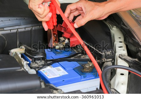 Car mechanic uses battery jumper cables charge a dead battery. - stock photo