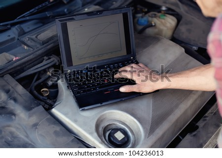Car mechanic with laptop checking enine - stock photo