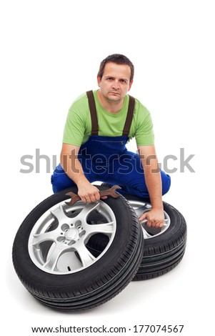 Car mechanic with new tires and spanner - isolated - stock photo