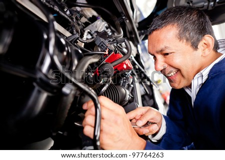 Car mechanic working at the auto repair shop - stock photo