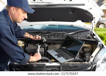 Car mechanic working in auto repair shop. - stock photo