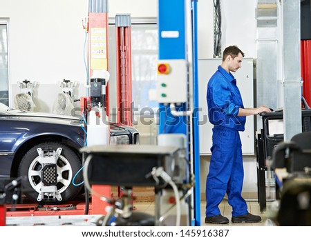 car mechanic working with computer during suspension adjustment and automobile wheel alignment work at repair service station - stock photo