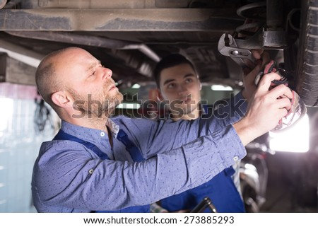 Car mechanics checking up pressure in tires at workshop - stock photo