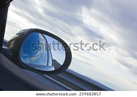 Car mirror on a diagonal cloudscape with motion blur. - stock photo