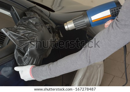 Car mirror wrapped in adhesive foil or film by car wrapping professional - stock photo
