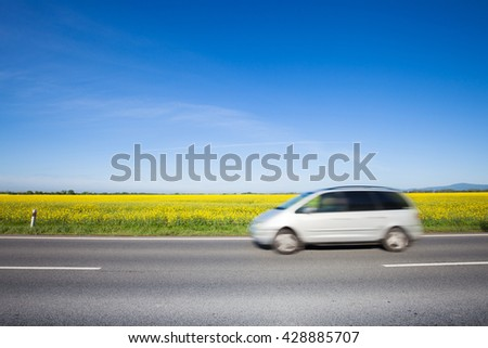 Car moving on the beautiful yellow field countryside road - stock photo