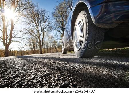 Car on asphalt road in spring morning - stock photo