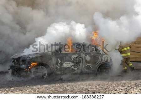 Car on fire being rescued A firefighter runs bravely to spray water over the burning car. One cannot even recognize the face of the brave firemen since the smoke cloud was huge.   - stock photo