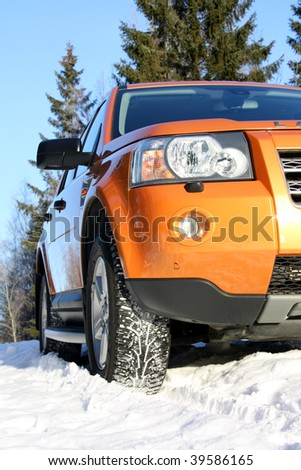 Car on snow having winter tires with spikes - stock photo