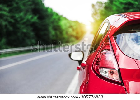 Car on the empty road at sunset. - stock photo