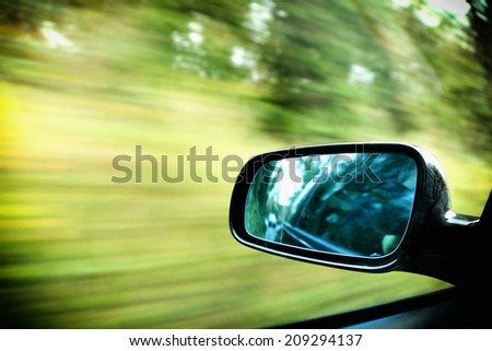 car on the road wiht motion blur background and rear view mirror - stock photo