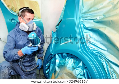 Car painter at work spraying blue. - stock photo