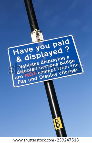 Car park sign. Have you paid & displayed your ticket? Money concept against a clear blue sky background - stock photo