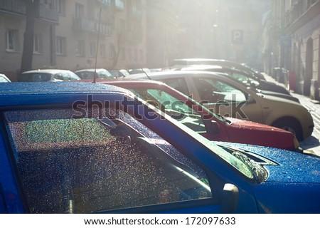 Car parking on the Krakow street in the rain. Poland - stock photo