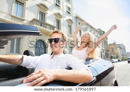 Car people - man driving with happy woman. Male driver wearing sunglasses. Young couple having fun in car driving on travel vacation together. Lifestyle with beautiful cheerful lovers. - stock photo