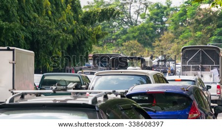 Car queue in the bad traffic road contrast with the green trees - stock photo