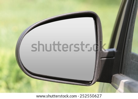car rearview mirror triangular shape on a blurred green background - stock photo