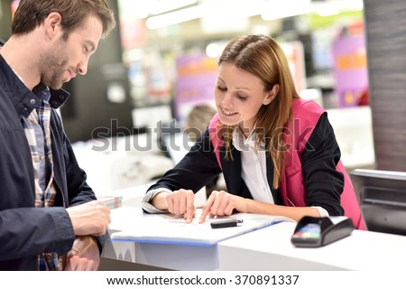 Car rental assistant giving information to customer - stock photo