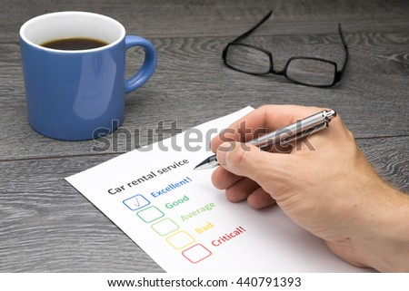 Car rental service offering excellent service. Customer filling out survey form while having a coffee - stock photo