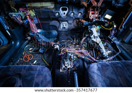 car repair & electric wiring system showing colorful wire in old car, interior view - stock photo