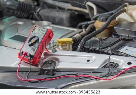 Car repair service, Auto mechanic checking a car battery level by voltmeter - stock photo