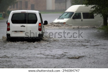 car rides in heavy rain on a flooded road - stock photo