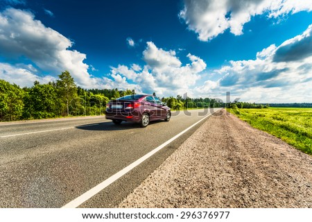 Car rides on a rural road that runs through the fields and forests - stock photo