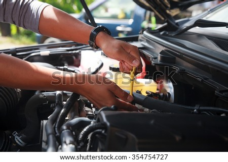 Car's mechanic checking oil. - stock photo