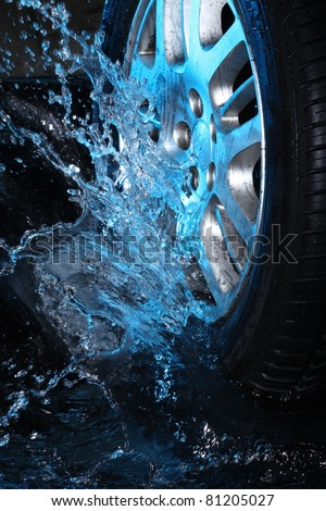 Car's wheel  with blue water on  black background - stock photo
