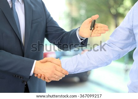 Car salesman handing over the keys for a new car to a young businessman . Handshake between two business people. Focus on a key - stock photo