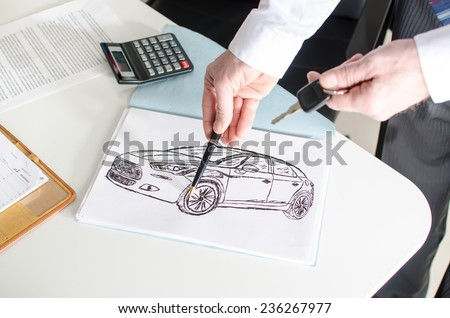 Car salesman showing a car design at the dealership office - stock photo
