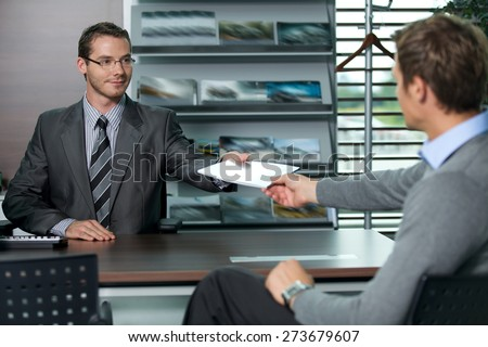 Car salesperson giving catalog to businessman - stock photo