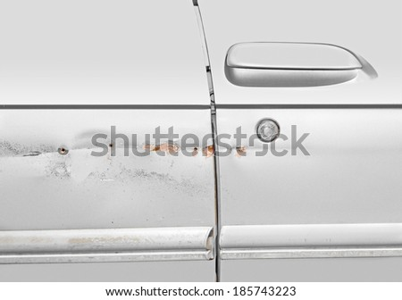 Car scratches dents and holes. Silver color vehicle needs repair. Passenger side door damage. Rust, chipped paint. Putty fills some holes. Door handle and keyhole shown. Horizontal photo.  - stock photo