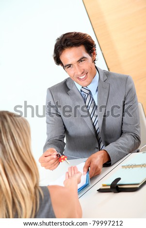 Car seller giving car keys to woman - stock photo