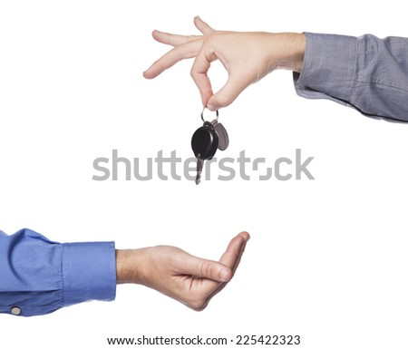 Car seller just about to drop the keys to the buyers hand. - stock photo