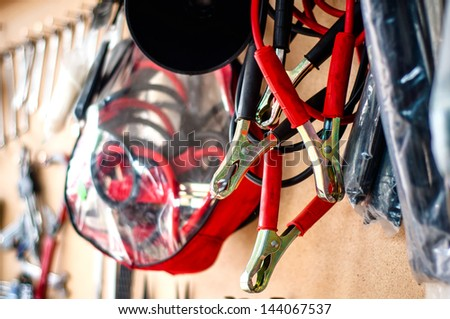 Car service wall with different tools, close-up of jump-start cables for car battery - stock photo
