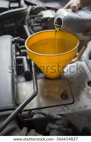 Car servicing mechanic pouring lubricant oil to engine.  - stock photo