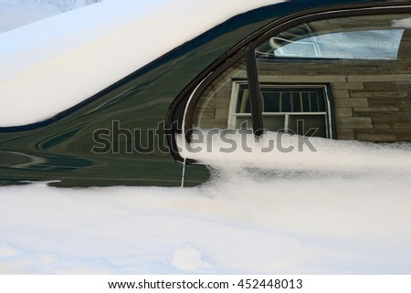 Car stuck in the deep snow after the snowstorm reflects the buildings around. - stock photo