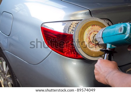 Car tail light with power buffer machine at service station - a series of CAR CARE images. - stock photo