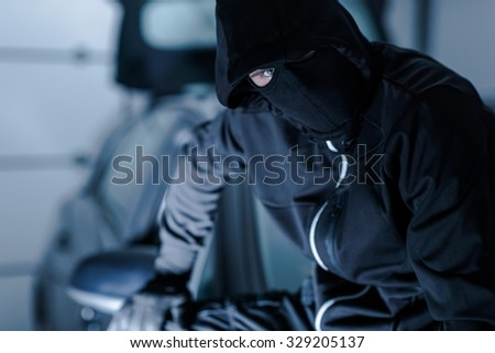 Car Theft Portrait. Successful Theft in Black Face Mask Seating on a Freshly Stolen Car. - stock photo