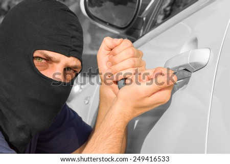 Car theft with a bloody green eyes. - stock photo