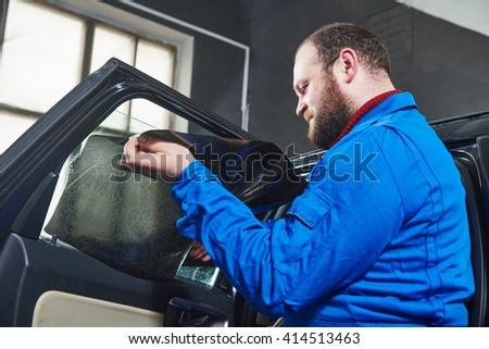 car tinting. Automobile mechanic technician applying foil  - stock photo