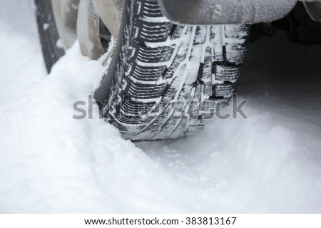 Car tire in the snow close up - stock photo