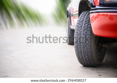 Car tire on the road with motion blur road background - stock photo