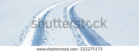 Car tire tracks in snow - stock photo