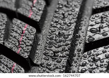 Car tires close-up Winter wheel profile structure with waterdrops  - stock photo
