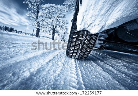 Car tires on winter road - stock photo