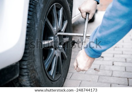 car tires prepared to replace in a garage - man hand changing tire on white car - stock photo