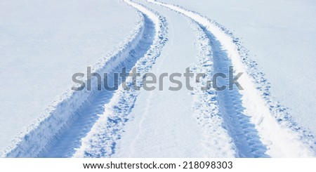 Car tracks in snow - stock photo