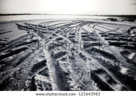 Car tracks in snow close to winter beach - stock photo